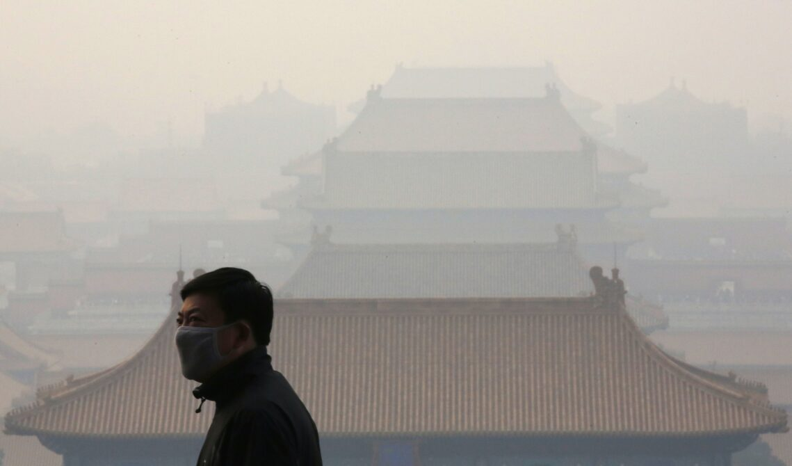 A man wearing a mask is seen in front of the Forbidden City from the top of Jingshan Park on a hazy day in Beijing