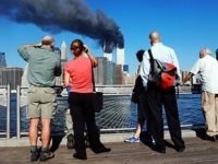 Pedestrians on the waterfront in Brooklyn, New York, look across the East River to the burning World Trade Center towers 11 September, 2001 after a terrorist attack.  AFP PHOTO  Henny Ray ABRAMS / AFP PHOTO / HENNY RAY ABRAMS