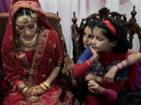 Pakistani girls look at bride Najma Khalil (L) during her wedding party in Islamabad on January 24, 2010. Most marriages in Pakistan are arranged. Arranged marriages have been an integral part of Pakistani society for years and it is traditional for people to have their marriages planned by their parents and other respected family-members. The bride and groom and two witnesses from the relatives or friends must sign the marriage documents in the presence of the Imam or a Molana for the Nikah, which is the Islamic marriage contract. The bride traditionally wears a red, pink or purple cloth called as gharara or lehenga that is usually accompanied with heavy gold jewellery. AFP PHOTO/BEHROUZ MEHRI (Photo credit should read BEHROUZ MEHRI/AFP/Getty Images)